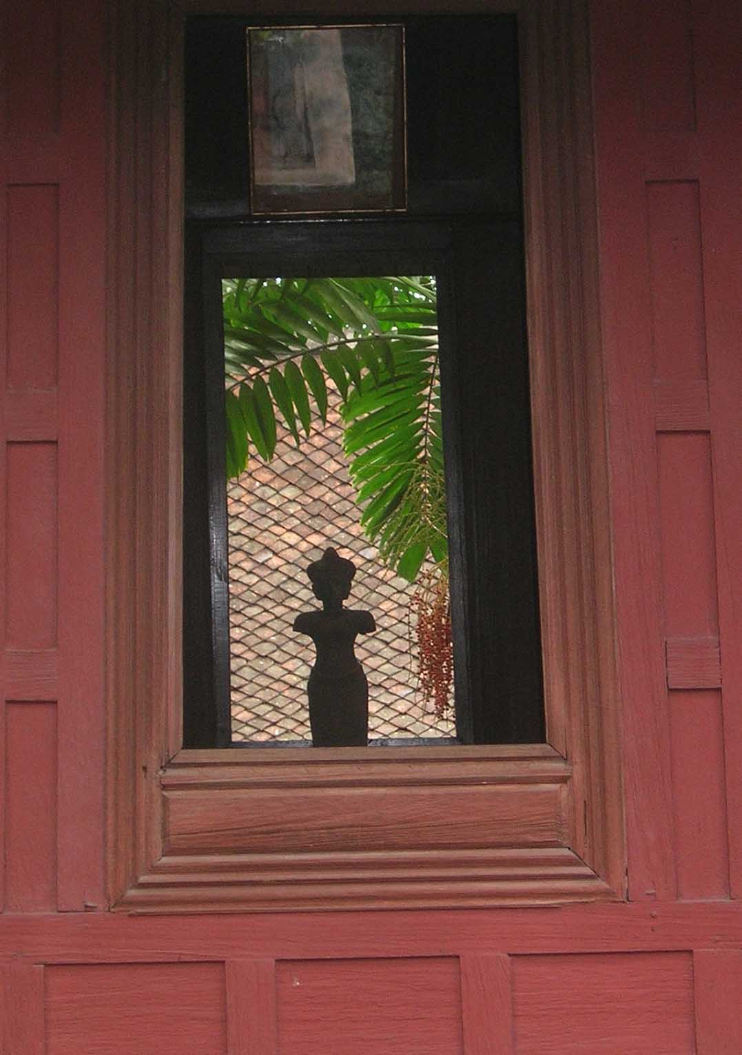 An antique Buddha image framed by a 100-year-old window at Jim Thompson's house.